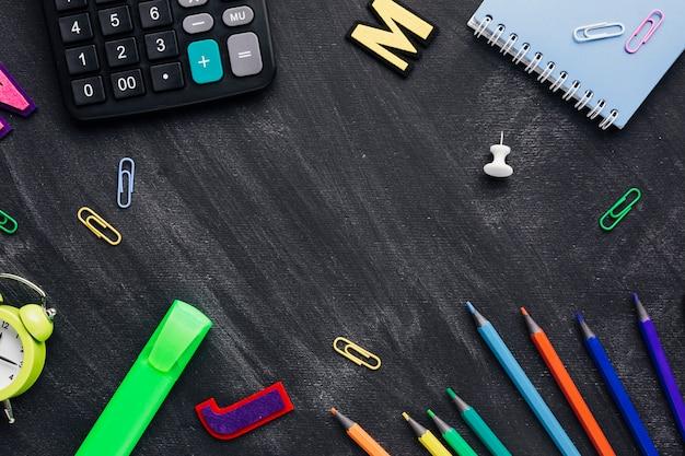 School supplies scattered like frame on chalkboard