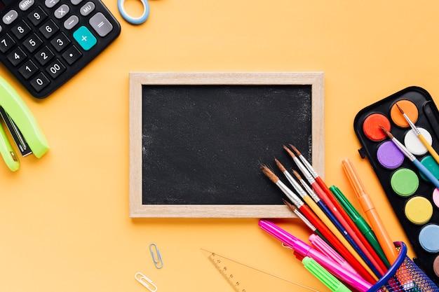 School supplies scattered round blank framed chalkboard on yellow desk