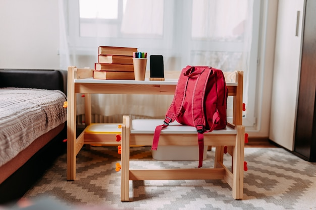 School supplies on the school desk. red backpack, white headphones, notebook, big red books, pens in the jar lay on the white school desk.