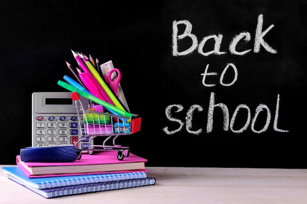 School supplies and shopping trolley on the background of the school board