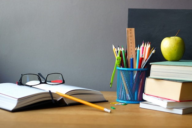 School supplies, stack of books, chalkboard and open book with glasses on a wooden surface