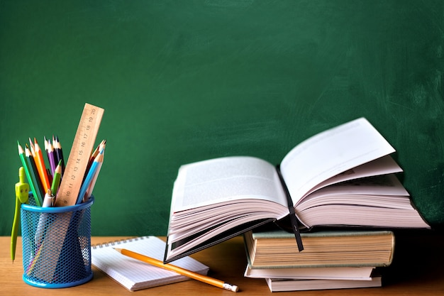 School supplies, stack of books, chalkboard and open book on a wooden surface