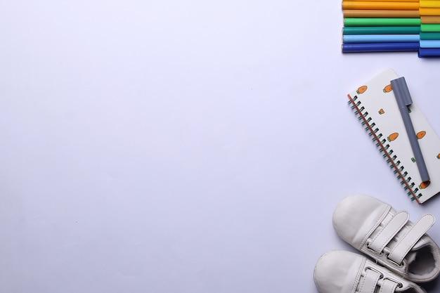 Школьные принадлежности канцелярские товары и обувь на белом фоне и место для подписи сверху