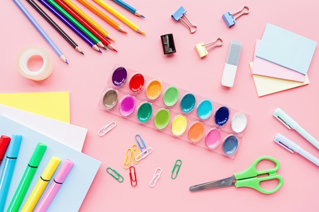 School supplies stationery, colour pencils, paints, paper on pink