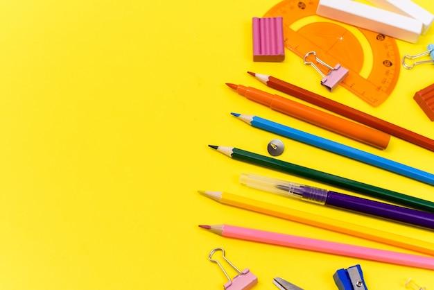 Школьные принадлежности канцтовары на желтом фоне. вид сверху