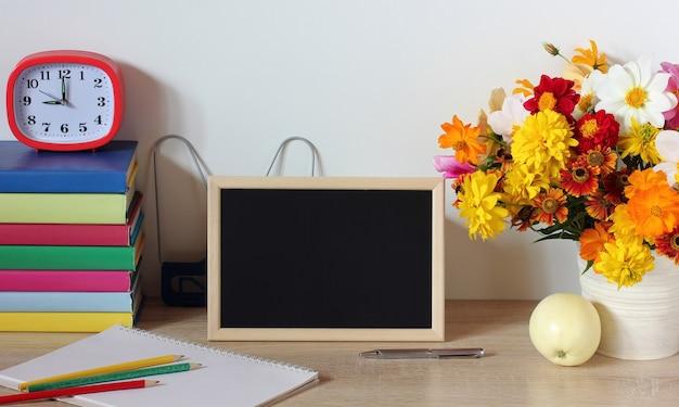 学校は、テーブルに黒い空白の背景の黒板が付いた木製のフレームで静物を供給します学校のモックアップ学校に戻る9月1日知識の日教師の日
