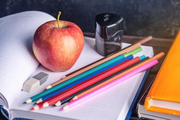 School supplies on the table. books, pencils and apples is a collection of the student.