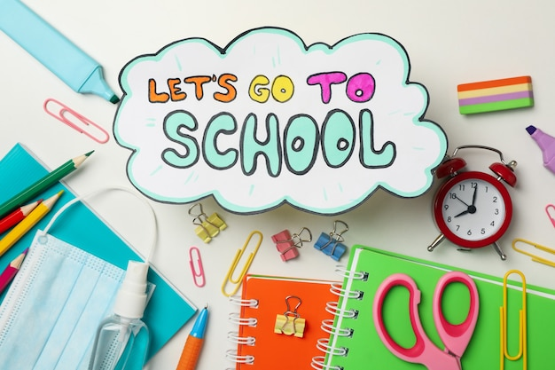 School supplies and text lets go to school on white
