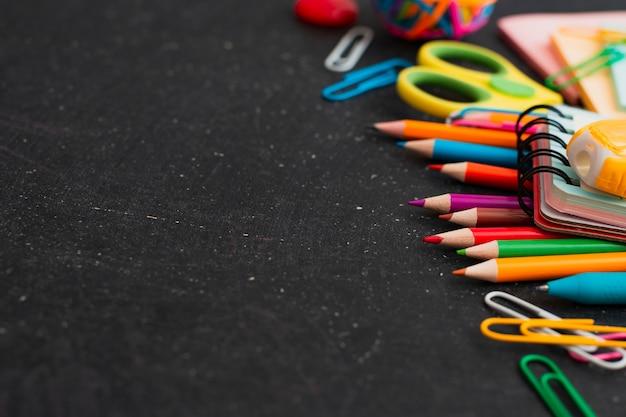 Взгляд сверху школьных принадлежностей на предпосылке доски. свободное место.