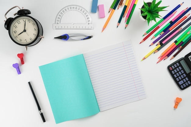 School supplies on a white background from above with place for text.