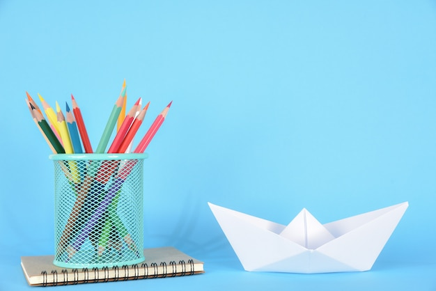 School supplies and white paper ship on blue