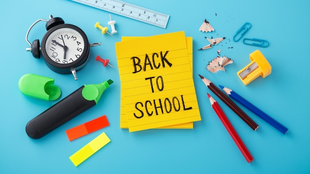 School supplies with back to school message on sticky note