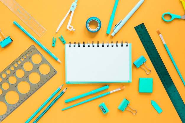 School supplies with blank notebook in center