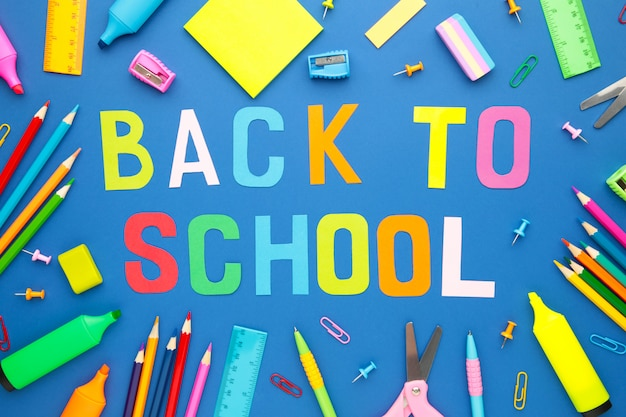 School supplies with inscription back to school on blue wall