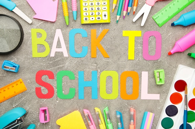 School supplies with inscription back to school on grey concrete background