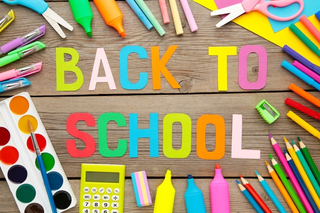 School supplies with inscription back to school on grey wooden background