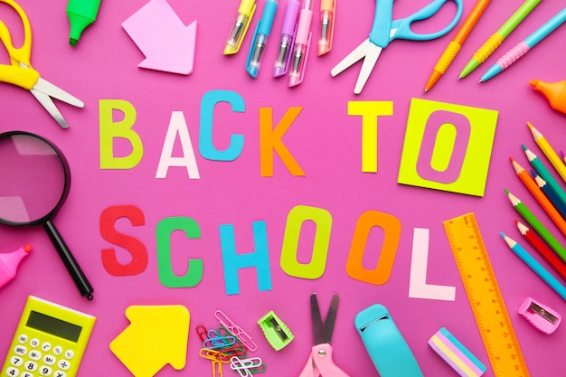 School supplies with inscription back to school on pink concrete background