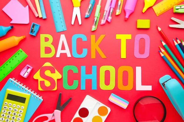 赤の背景に学校に戻る碑文と学用品