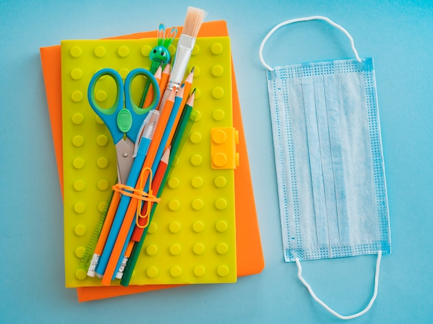 School supplies with medical face mask on blue blue. flat lay, top view, layout, template, free space