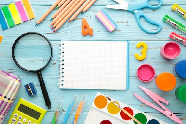 Школьные принадлежности с тетрадью на синем деревянном фоне. обратно в школу. плоская планировка. вид сверху