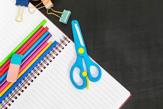 School supplies with notebook, scissors, paper clips, colored pencils