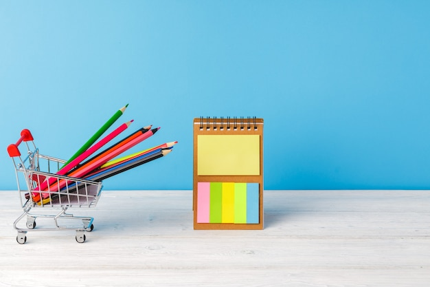 School supplies on wooden desk against blue background, front view