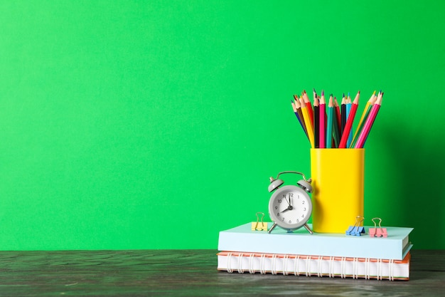 School supplies on wooden table against green