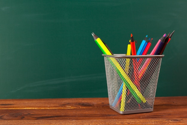 School supplies on a wooden table and blackboard background