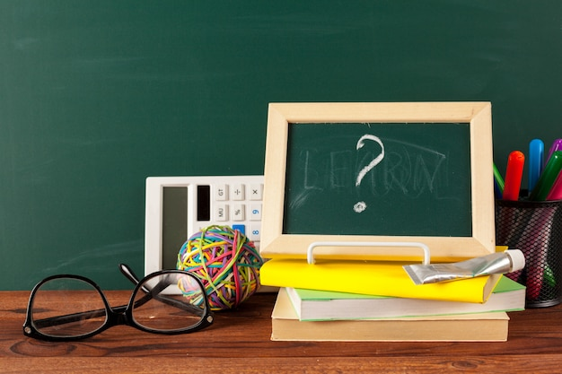 School supplies on a wooden table and blackboard