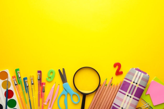 School supplies on yellow background. back to school concept.