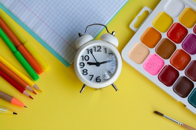 School supplies on yellow, pen, pencils, markers, watercolors, notebook and alarm clock, flat lay
