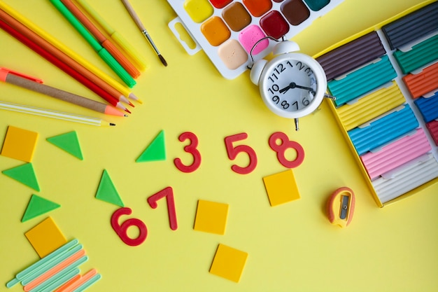 School supplies on yellow, pen, pencils, markers, watercolors, plasticine, sharpener, numbers, geometric shapes, counting sticks, alarm clock, plasticine, flat lay