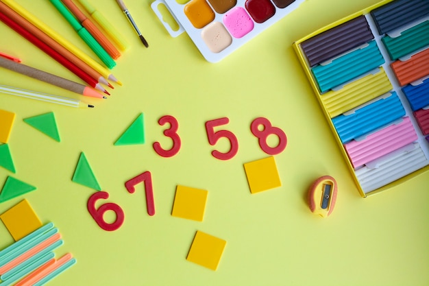 School supplies on yellow, pen, pencils, markers, watercolors, plasticine, sharpener, numbers, geometric shapes, counting sticks, flat lay