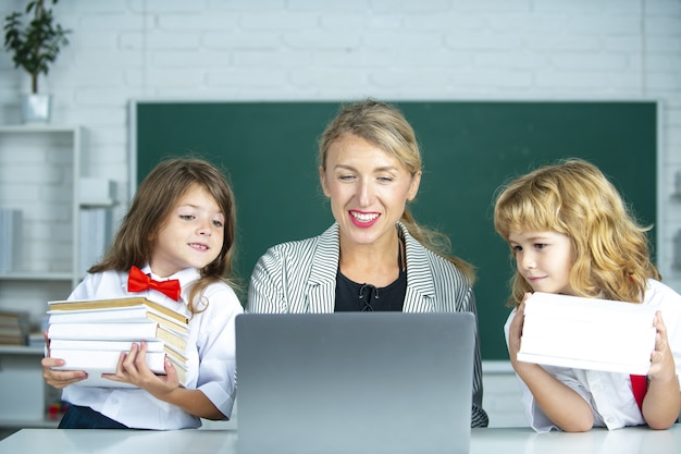 학교 교사와 학교 아이들, 귀여운 소녀와 소년. 책상에서 노트북을 사용하는 초등학교 학생들과 교사.