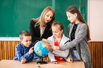 School teacher and students working with globe