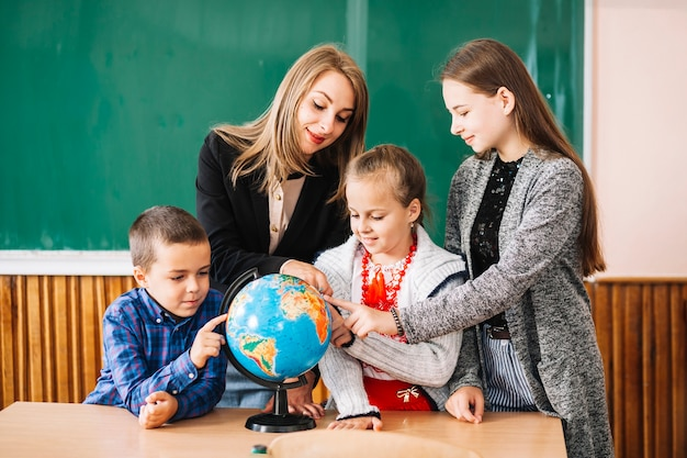 Школьный преподаватель и студенты, работающие с земным шаром