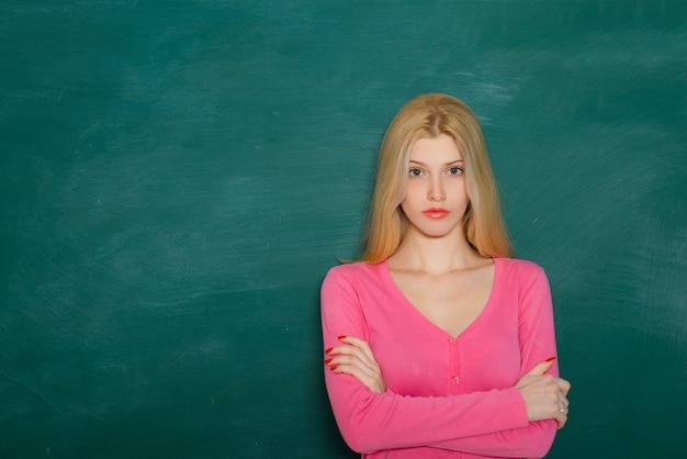 黒板の背景にクラスの学校の先生。プロのポートレート。