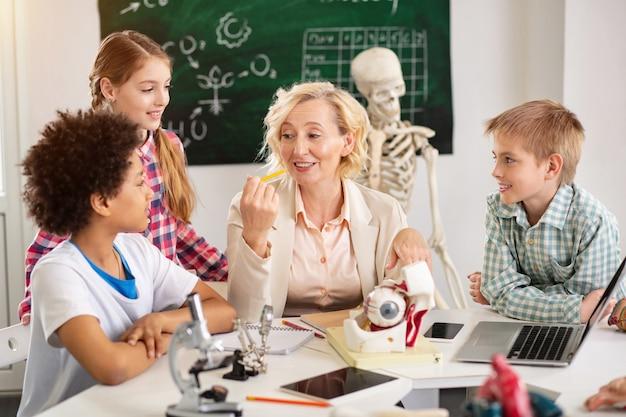 Школьный учитель. милая счастливая женщина сидит за столом во время урока биологии