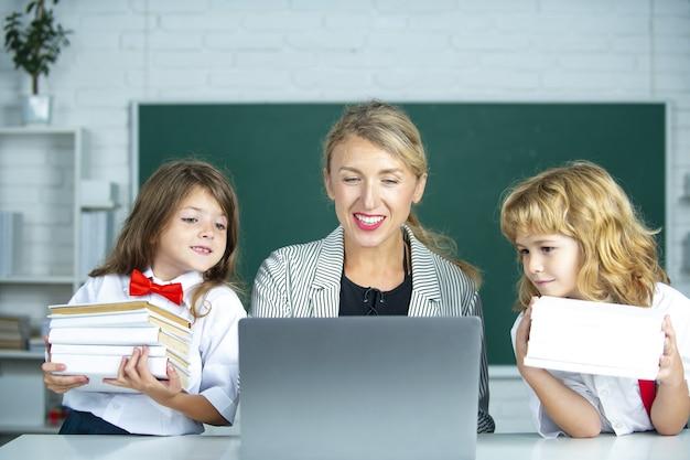 School teacher and school kids, cute girl and boy. teacher with elementary school pupils using laptop at desk.