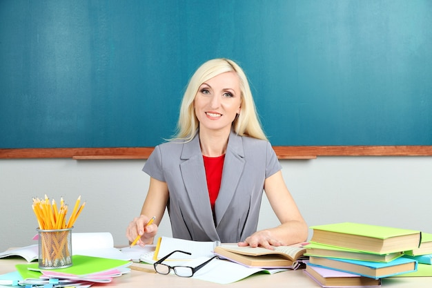 School teacher sitting at table on blackboard