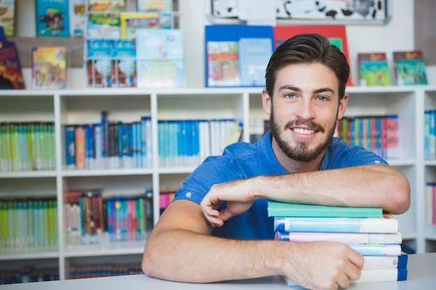 Школьный учитель сидит с книгами в библиотеке