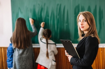 School teacher with clipboard on background of blackboard and students