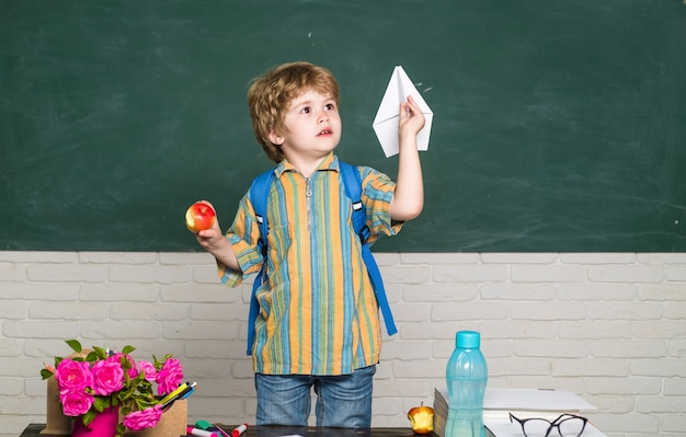 School time boy with paper airplane in classroom back to school schoolboy education september copy