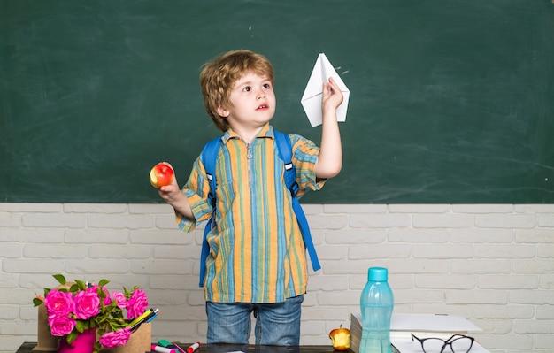 教室で紙飛行機を持った学校時代の少年が学校に戻る男子生徒教育9月のコピー
