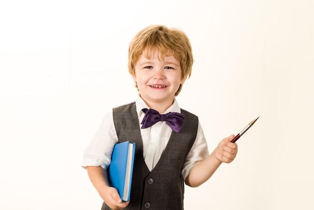 本とペンで男子生徒を笑顔の学校の時間小学校の子供メモ帳教育9月
