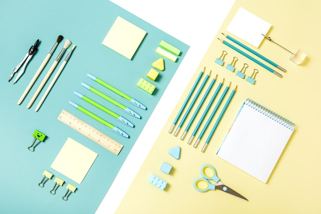 School tools on blue and yellow background. top view.back to school, school supplies - pencils and paints, ruler and eraser, paper clips and scissors, notepads and notebooks.