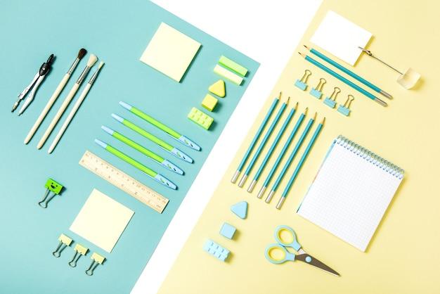 青と黄色の背景に学校のツール。 top view.back to school、学用品-鉛筆と絵の具、定規と消しゴム、ペーパークリップとはさみ、メモ帳とノート。