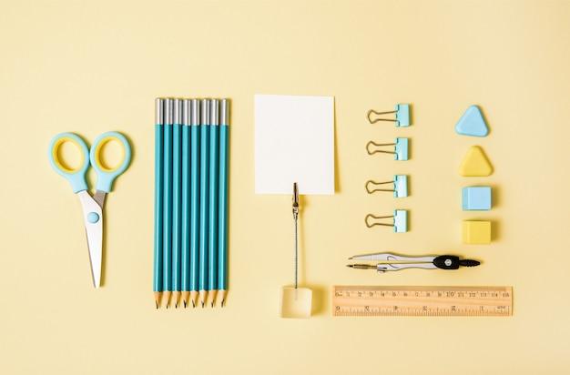 青と黄色の背景に学校のツール。上面図knolling.backto school、学用品-鉛筆と塗料、定規と消しゴム、ペーパークリップとはさみ、メモ帳とノート。