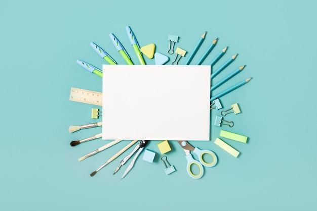 青い背景の学校のツール。 top view.back to school、学用品-鉛筆と絵の具、定規と消しゴム、ペーパークリップとはさみ、メモ帳とノート。