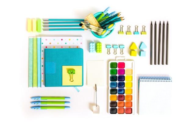 白い背景の上の学校のツール。 top view.back to school、学用品-鉛筆と絵の具、定規と消しゴム、ペーパークリップとはさみ、メモ帳とノート。